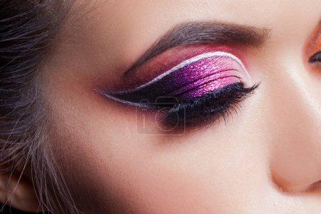 惊人的明亮的眼妆。带有紫色色彩和不寻常的白色箭头的眼影_高清图片_邑石网