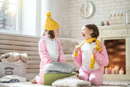Cute little girls sitting on the floor and holding warm knitted clothes. Kids enjoying the winter.