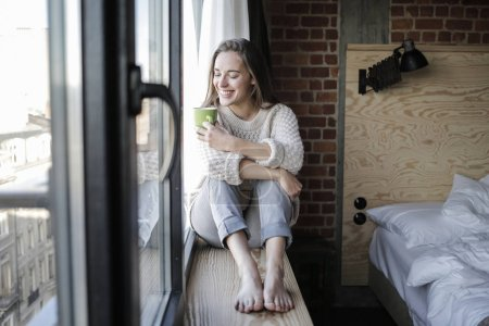Happy young woman sitting in a window will with a cup of drink.
