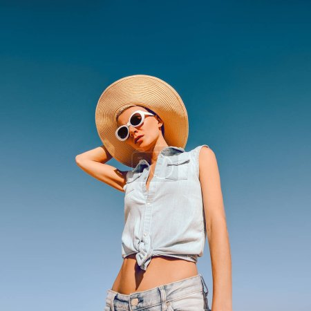 Girl in fashion accessories. Hat and sunglasses and jeans outfit. Beach summer mood