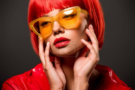 close-up portrait of seductive young woman in red latex jacket and vintage yellow sunglasses isolated on grey