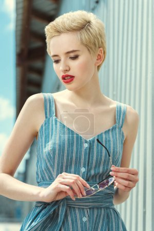 attractive girl with short hair posing in trendy blue dress