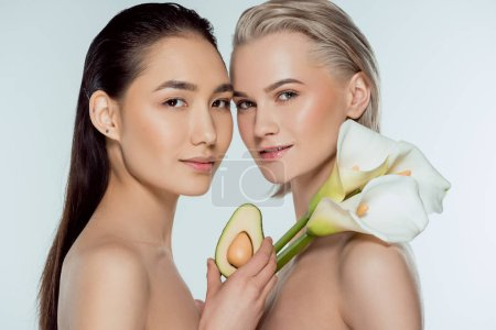 beautiful multicultural naked girls posing with avocado and calla flowers, isolated on grey, skin care concept