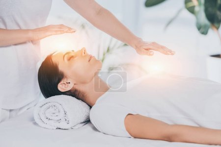cropped shot of reiki healer doing therapy session to calm young woman with closed eyes