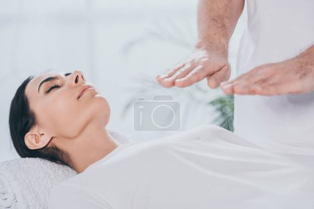 cropped shot of young woman with closed eyes receiving reiki healing session