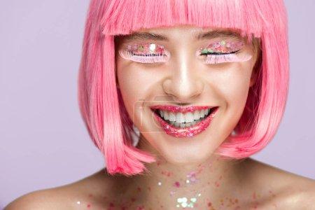 微笑迷人的女人与粉红色的头发, 闪闪发光的妆和长睫毛隔离在紫罗兰色