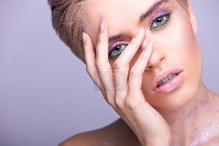 有吸引力的妇女与紫罗兰色闪光在脖子和短的头发触碰的面孔在紫罗兰色