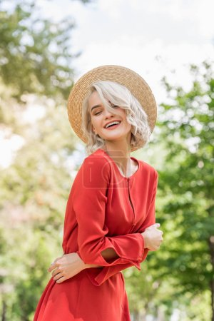smiling attractive girl in red dress and straw hat in park