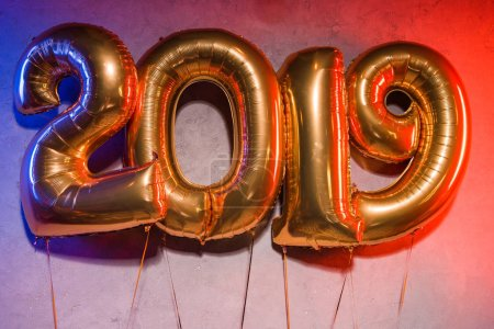 golden 2019 sign helium balloons with blue and red light on grey