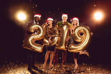 happy friends in santa hats holding 2019 new year golden balloons on confetti