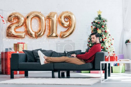 man using laptop on sofa at home with christmas tree and 2019 golden balloons
