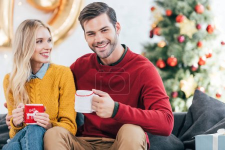 smiling couple with cups of coffee at home on christmas eve