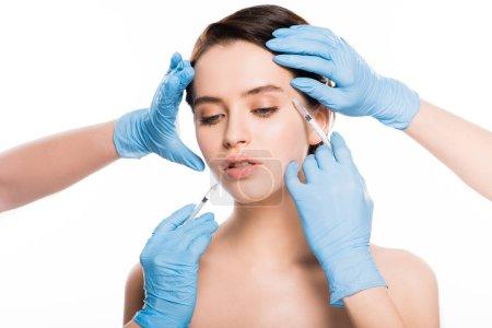 在乳胶手套的美容师的裁剪视图触摸有吸引力的女孩的脸, 而持有注射器隔离在白色_高清图片_邑石网