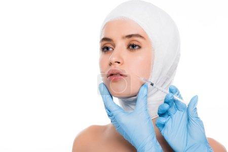 在乳胶手套的美容师的裁剪视图与包扎头查出在白色的妇女的脸附近 _高清图片_邑石网