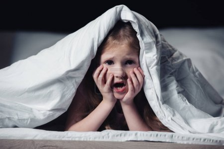 害怕的孩子尖叫和手牵手的脸,而躲在毯子下孤立在黑色_高清图片_邑石网