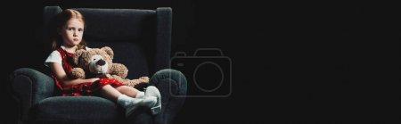悲伤,孤独的孩子坐在扶手椅与泰迪熊,看着相机孤立在黑色_高清图片_邑石网