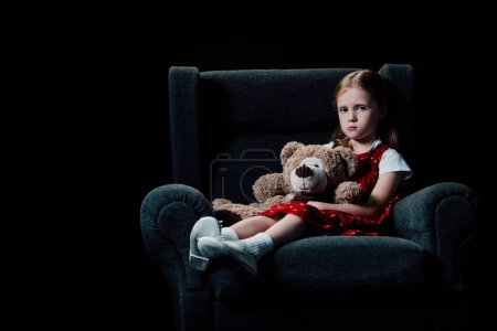 悲伤,孤独的孩子坐在扶手椅上,抱着泰迪熊孤立在黑色_高清图片_邑石网