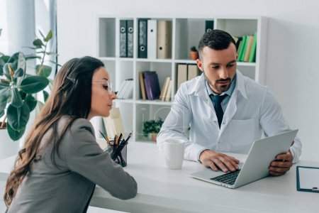 patient and general practitioner looking at laptop in clinic