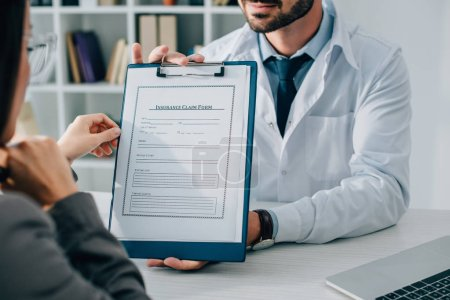 cropped image of general practitioner showing insurance claim form to patient in clinic