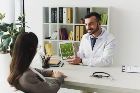 smiling doctor showing patient gadget with pulse appliance in clinic