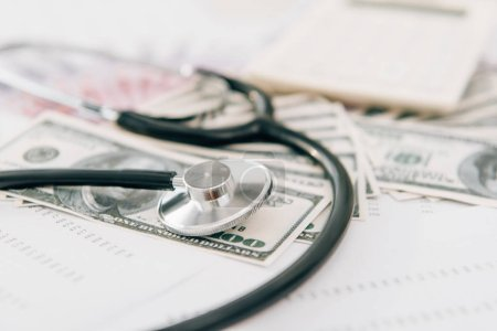 selective focus of stethoscope and dollar banknotes on table in clinic, health insurance concept