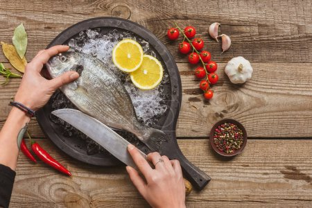 cropped image of tattooed woman cutting raw fish by knife on wooden table