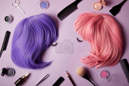 粉红色和紫色假发, 假睫毛, 化妆工具和化妆品在紫色的顶部视图