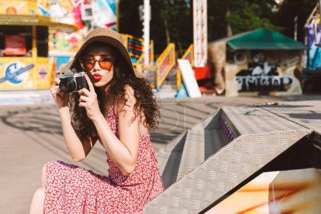 美丽的女士与深色卷曲的头发在太阳镜和帽子坐在手里的小相机和花时间在游乐园与景点背景