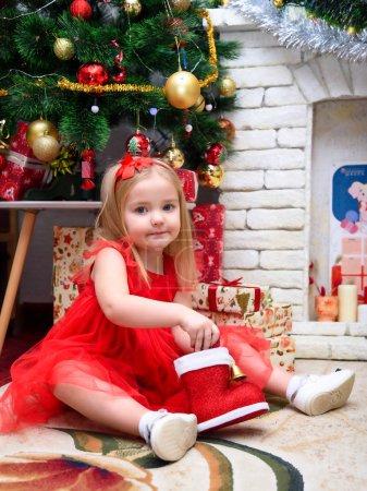 一个可爱美丽的女孩在新的一年与礼物的概念肖像在圣诞树的背景下, 在一个时尚的红色礼服。她坐在不同的情绪._高清图片_邑石网