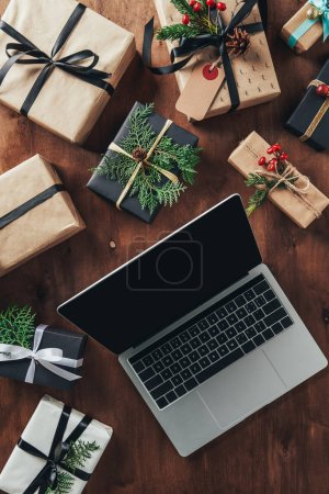 top view of christmas presents and laptop with blank screen on wooden background