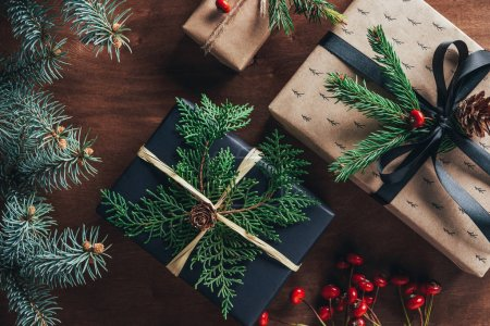 top view of christmas gift boxes with fir branches and decorative berries on wooden background