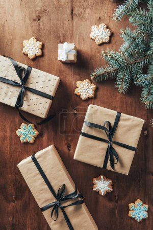 flat lay with christmas gift boxes, fir branch and cookies on wooden background