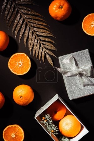 top view of fresh tangerines, decorative twig and silver gift box on black background
