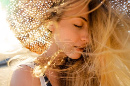 portrait of beautiful woman in straw hat with eyes closed