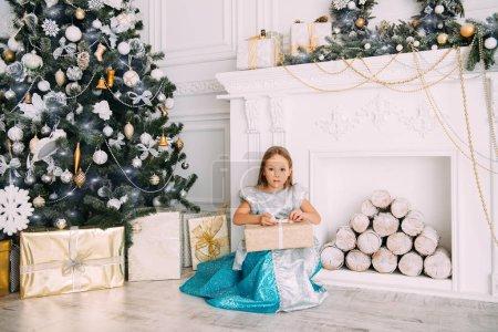 可爱的六岁的女孩坐在圣诞树旁边的一个优雅的礼服与礼品盒。圣诞节时尚概念经典豪华室内装饰圣诞._高清图片_邑石网