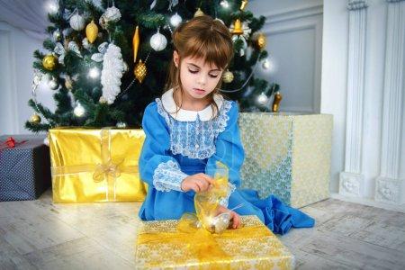可爱的五岁的女孩坐在圣诞树旁边的一个优雅的礼服与礼品盒。圣诞节时尚概念经典豪华室内装饰圣诞._高清图片_邑石网