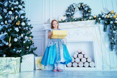 可爱的六岁的女孩站在圣诞树旁边, 穿着一件优雅的连衣裙, 配有礼品盒。圣诞节时尚概念经典豪华室内装饰圣诞._高清图片_邑石网