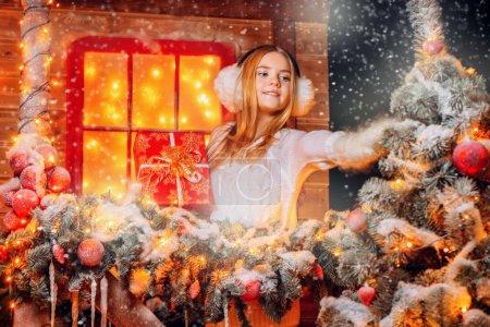 漂亮的小女孩站在她的房子附近的圣诞装饰毛皮耳和手套。冬季保暖配件。圣诞快乐, 新年愉快._高清图片_邑石网