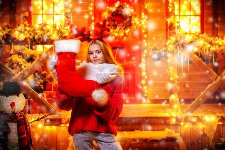 漂亮的小女孩站在她的房子附近的圣诞装饰与驯鹿鹿角的头部和手持圣诞袜。圣诞快乐, 新年愉快._高清图片_邑石网