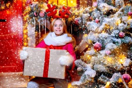 漂亮的女孩站在那里, 头上拿着驯鹿鹿角, 在为圣诞节装饰的房子附近的树周围放着一个礼品盒。圣诞快乐, 新年快乐._高清图片_邑石网