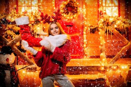 漂亮的女孩站在头上, 头上拿着一只圣诞靴子, 挂在装饰为圣诞节的房子的门廊上。圣诞快乐, 新年快乐._高清图片_邑石网