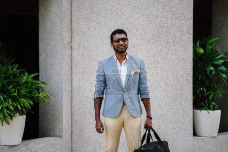 一个凉爽的印度亚裔男子的肖像靠在墙上的一天。他穿着休闲服和太阳镜。他正拿着一个健身房包, 因为他在阳光下闲逛, 等待着一个人
