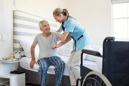 Smiling nurse assisting senior man to get up from bed. Caring nurse supporting patient while getting up from bed and move towards wheelchair at home. Helping elderly disabled man standing up in his bedroom.