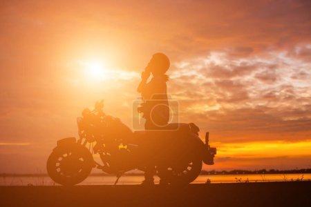 在日落的女人骑自行车的人