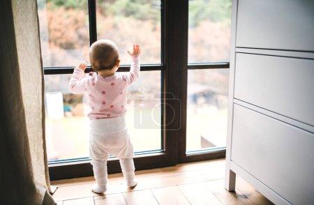 一个蹒跚学步的孩子站在窗边的地板上, 在家里