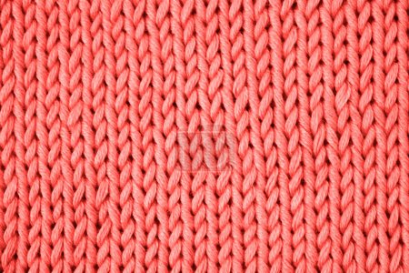 Trend concept color of the year 2019 Living Coral. Bright cotton knitting on knitting needles, needlework. Top view close up