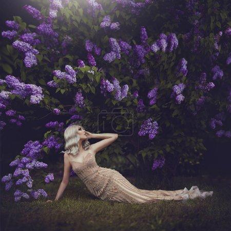 美丽的感性女孩在春天金发女郎。春天的风格。盛开的春天花园。一个穿着金色连衣裙的年轻女孩躺在盛开的紫色灌木丛下。