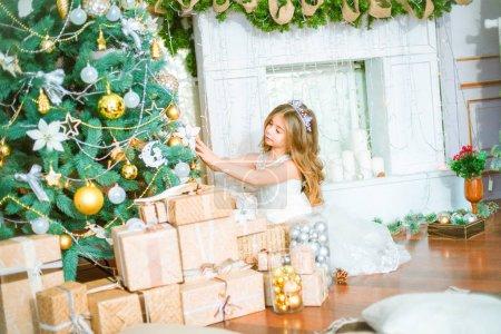 可爱的小女孩与长卷曲的头发在家里附近的圣诞树与礼品和花环和装饰的壁炉 _高清图片_邑石网