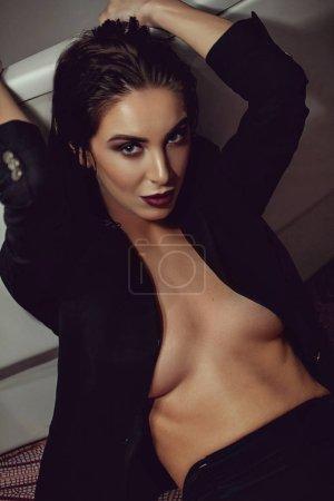 性感的黑发妇女摆在时尚的黑色礼服