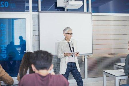 Pretty middle-aged Caucasian woman teacher teaching a lesson at high school.